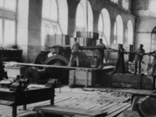 Ouvriers utilisant une sorte de bélier pour le montage du rotor du générateur